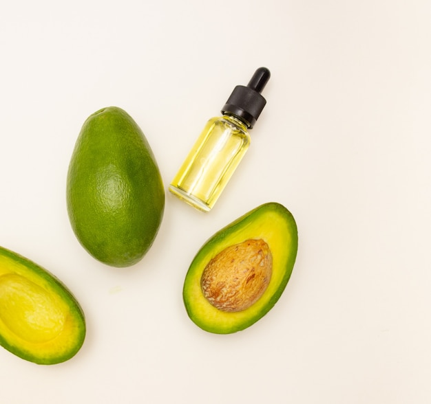 Glass bottle with pipette and avocado oil and avocado fruit on a light background, top view