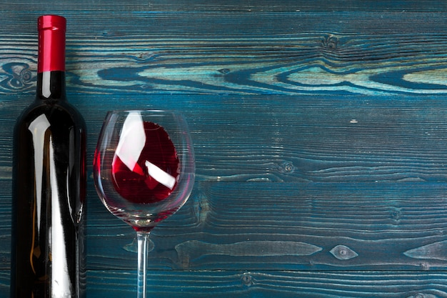 Glass and bottle with red wine on wooden background, top view