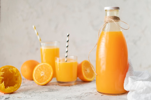 Glass bottle with a squeezed orange juice, sliced in a half oranges arounds