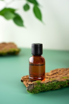 Glass bottle with tea tree essential oil standing on the bark of a tree cosmetic essence fresh green