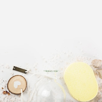 Glass bottle; yellow sponge and spa stones on spread salt at the bottom of the background