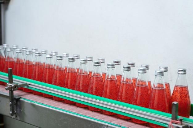음료 가공 공장의 생산 라인의 강철 컨베이어에 유리 병에 담긴 붉은 주스