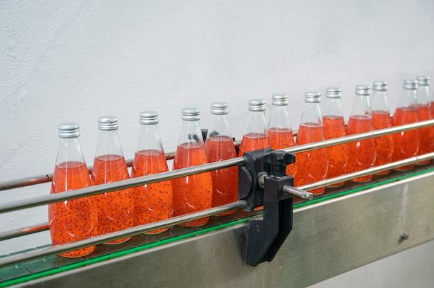 음료 가공 공장에서 생산 라인의 강철 컨베이어에 있는 유리병에 담긴 붉은 주스