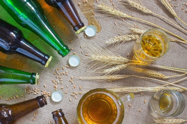 Стеклянные бутылки. кружка пива и два стакана пива. колоски пшеницы