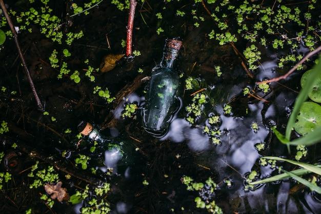 Стеклянные бутылки наполнены волшебными ингредиентами эликсиром таинственное озеро Premium Фотографии