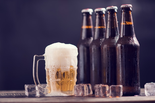 Glass bottles of beer with glass and ice on dark background