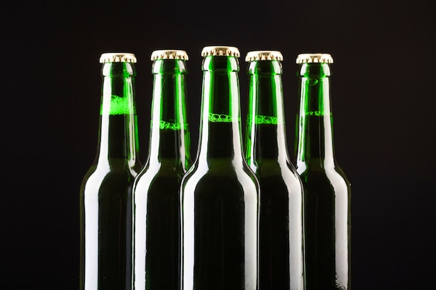 Glass bottles of cold beer are arranged in the center