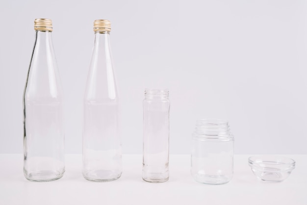 Glass bottles and cups on white background