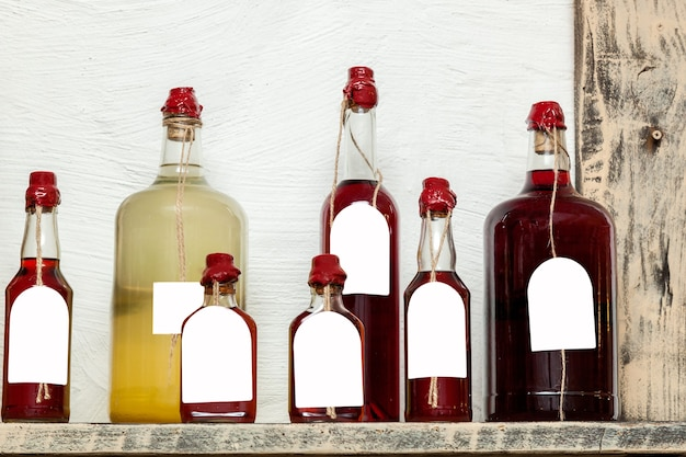 Glass bottles of different sizes with liqueurs sealed with wax