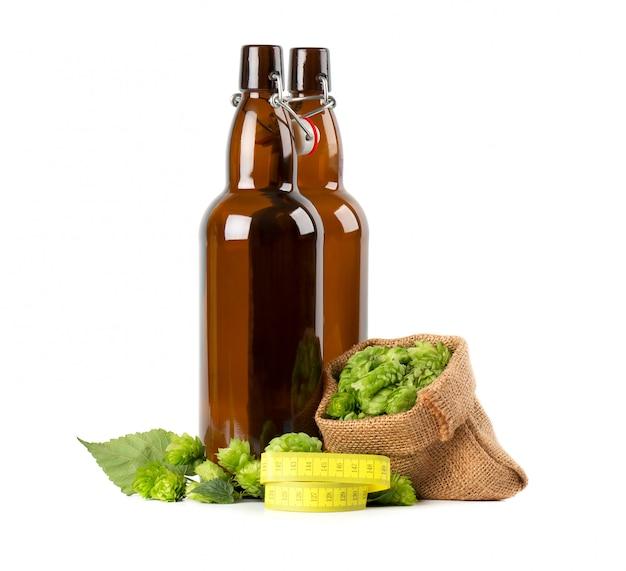 Glass bottles for kraft beer with fresh green branch of hops and yellow measuring tape, isolated . diet concept.