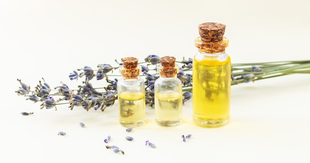 Glass bottles of lavender essential oil or natural perfume with dried lavender flowers