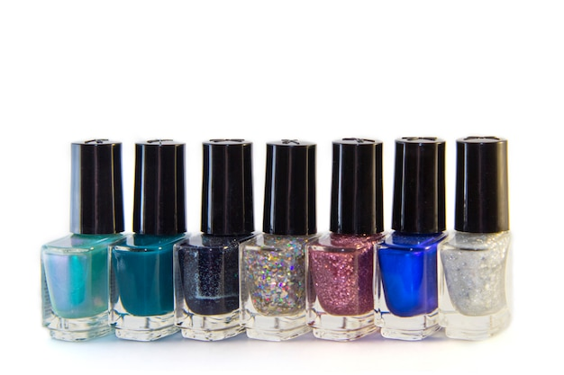Glass bottles of nail polish with fashionable different shades, isolated