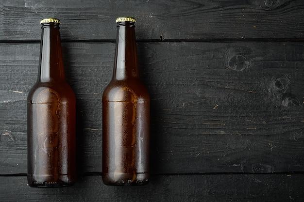 ビールセットのガラス瓶、黒い木製、上面図フラットレイ、コピースペース付き
