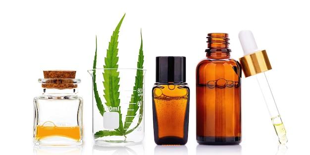 大麻油と麻の葉のガラス瓶は白で隔離。