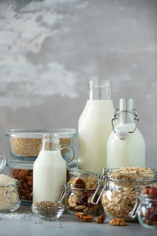 Стеклянные бутылки веганский завод молока и миндаль, орехи, кокос, конопляное молоко на сером фоне бетона.