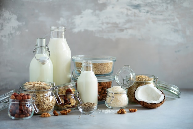 Glass bottles of vegan plant milk and almonds, nuts, coconut, hemp seed milk on grey concrete background.