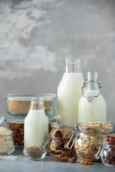 Glass bottles of vegan plant milk and almonds, nuts, coconut, hemp seed milk on grey concrete background.