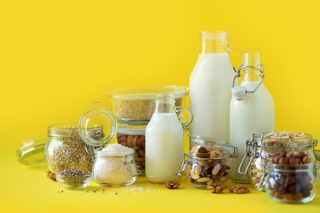 Glass bottles of vegan plant milk and almonds, nuts, coconut, hemp seed milk on yellow background.