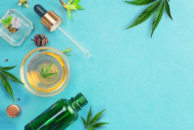 Стеклянные бутылки с маслом cbd, настойкой thc и листьями конопли на синем фоне. плоская планировка, минимализм. косметика cbd конопляное масло.