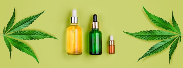 Glass bottles with cbd oil, thc tincture and hemp leaves on green
