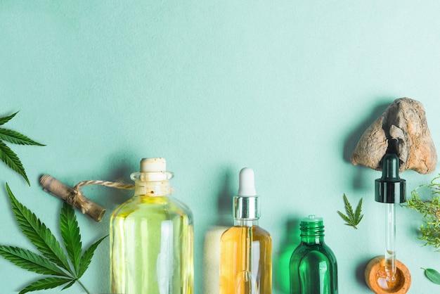 Cbdオイルのガラス瓶、青い背景にthcティンクチャー麻の葉。化粧品cbdヘンプオイル。