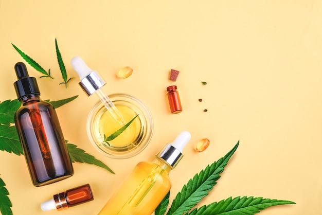 Glass bottles with cbd oil, thc tincture hemp leaves on a yellow background cosmetics cbd hemp oil