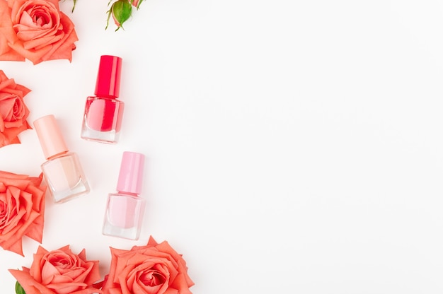 Glass bottles with colourful nail polish isolated on white background. pink, red and beige colours.