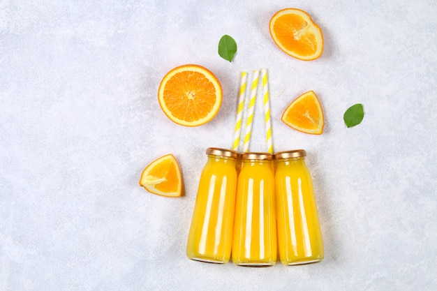 Glass bottles with fresh orange juice with orange slices and yellow tubes on a light gray table.