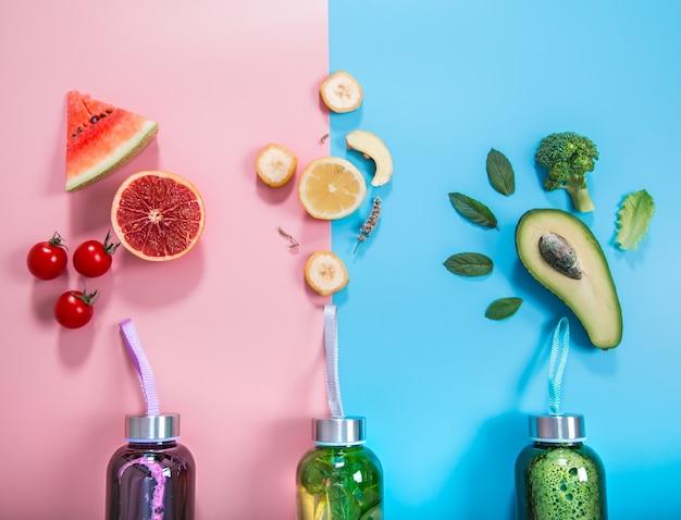Bottiglie di vetro con bevande naturali su uno sfondo colorato
