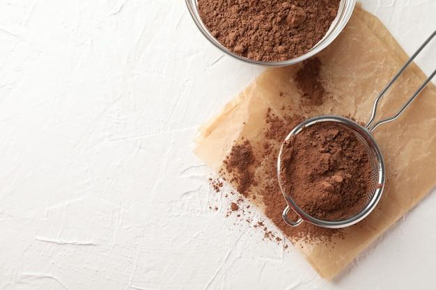 Стеклянная чаша и сито с какао-порошком, бумага для выпечки на белом, копией пространства