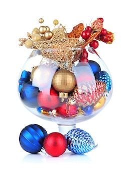 Glass bowl filled with christmas decorations, isolated on white