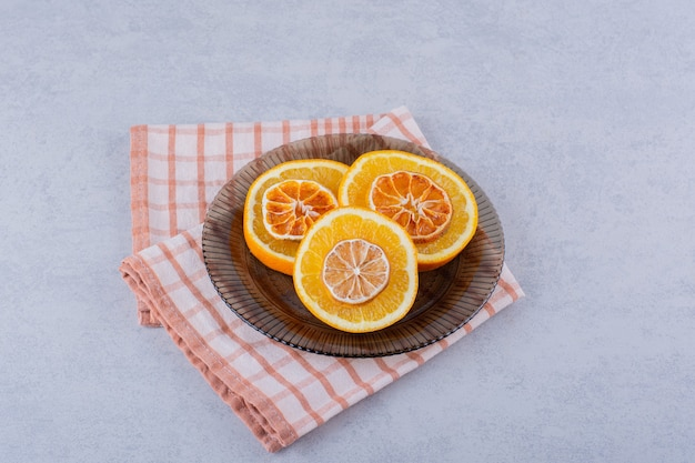 Glass bowl of fresh and dry orange slices on stone.