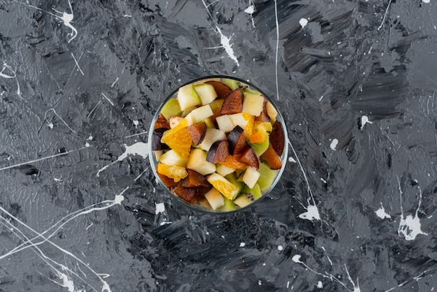 Glass bowl of fresh fruit salad on marble surface.