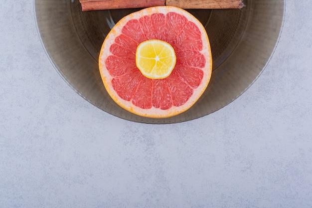 Glass bowl of fresh grapefruit slice with lemon on stone table.