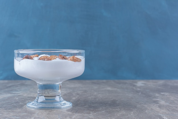 Una ciotola di vetro piena di sano yogurt con deliziosi cereali.