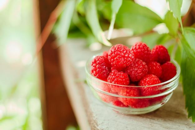 Glass bowl full of raspberries on wooden garden table