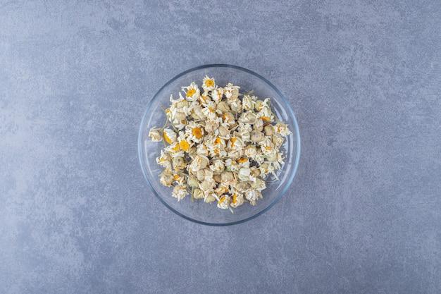 乾燥したカモミールの花でいっぱいのガラスのボウル