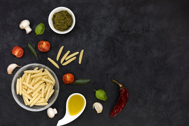 Glass bowl of garganelli pasta with sauce; mushroom; basil; tomatoes; red chili and garlic clove on black textured backdrop