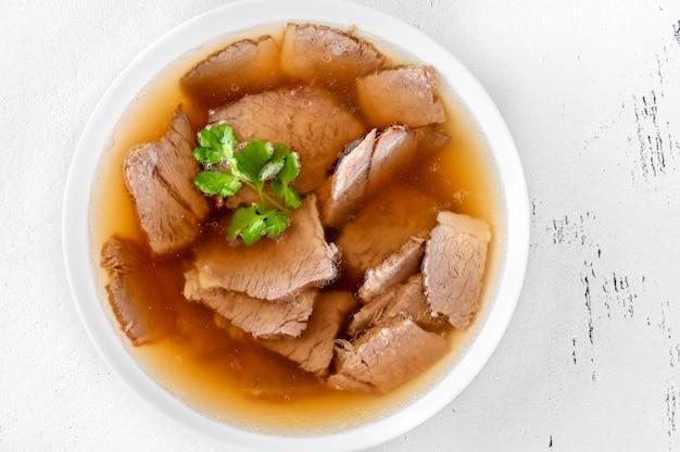 흰색 테이블에 고기와 쇠고기 뼈 국물의 유리 그릇