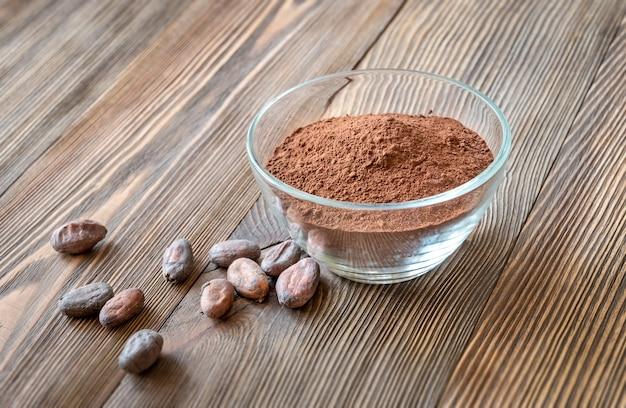 Стеклянная миска какао-порошка с какао-бобами