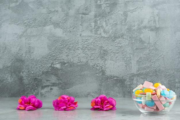 石の表面に花が付いたカラフルなチューインガムのガラスのボウル。