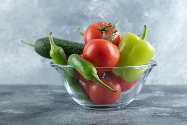 Стеклянная миска со свежими спелыми овощами на мраморном фоне