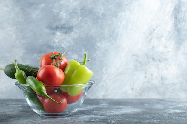 大理石の背景に新鮮な熟した野菜のガラスのボウル