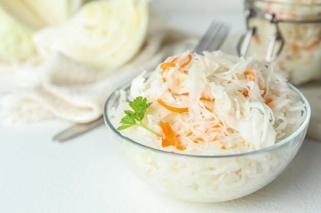 흰색 테이블에 맛있는 발효 양배추 유리 그릇, 근접 촬영