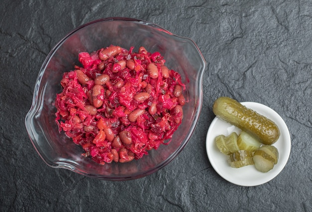 Glass bowl of pickled cabbage with red beans and cucumbers on black background