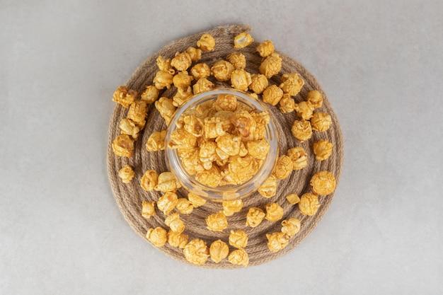 Ciotola di vetro posta su un sottopentola lavorato a maglia, riempita e circondata da popcorn ricoperti di caramello su un tavolo di marmo.
