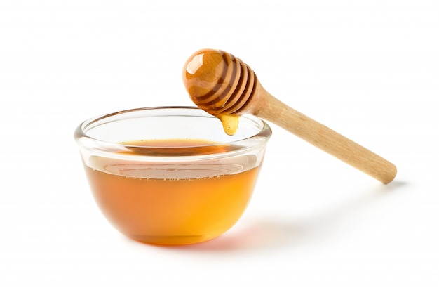 Glass bowl of pure honey with honey dipper isolated on white background.