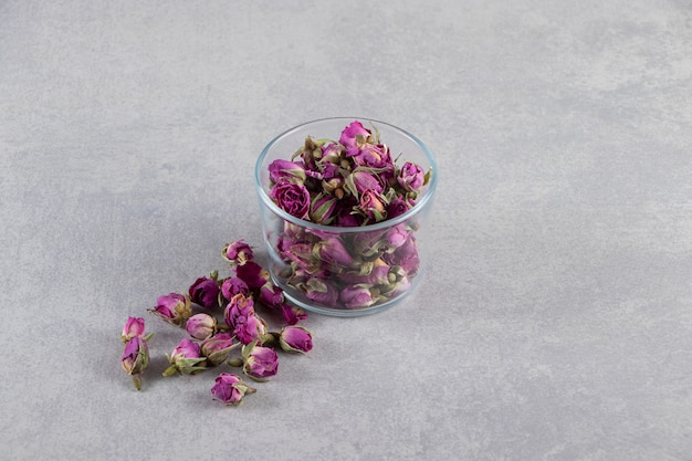 Glass bowl of purple budding roses placed on stone background.