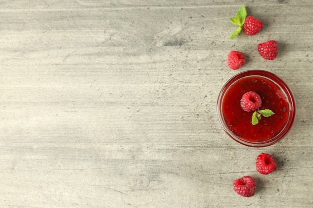 Glass bowl of raspberry jam with ingredients on gray textured background