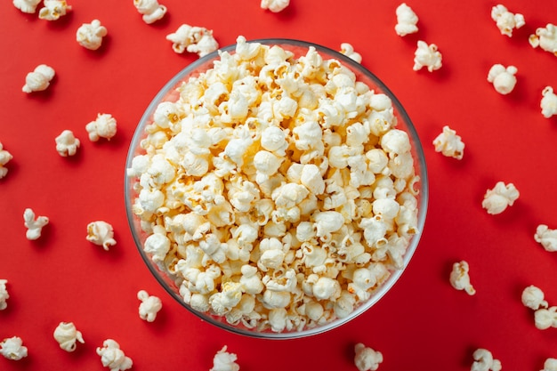 Glass bowl of salty popcorn on a red background